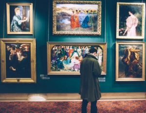 Man standing in front of Fine paintings in decadent museum